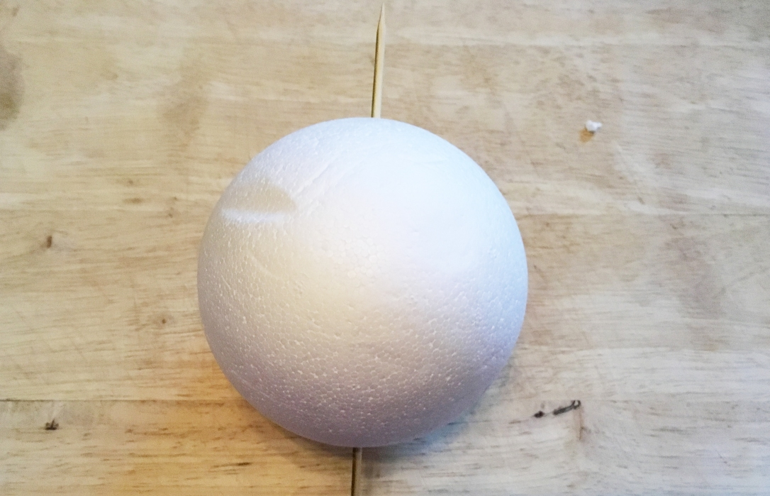 Larger polystyrene ball is pierced with a skewer