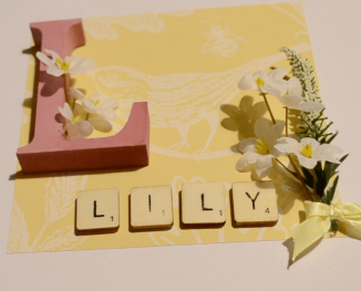 Insert of a box frame including a wooden letter, silk flowers and scrabble letters spelling out, Lily