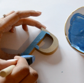 A close up of a letter being painted blue